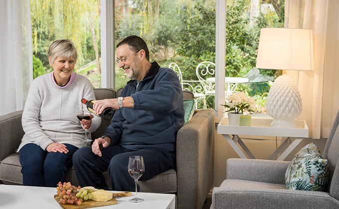 Couple enjoying wCouple enjoying wine on their couch at Pinoak Tiers Stirling Retirement Village