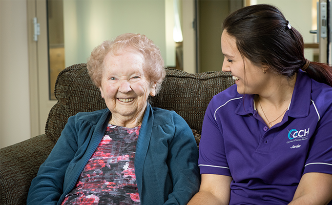 Resident and carer smiling on couch at Onkaparinga Valley Woodside nursing home