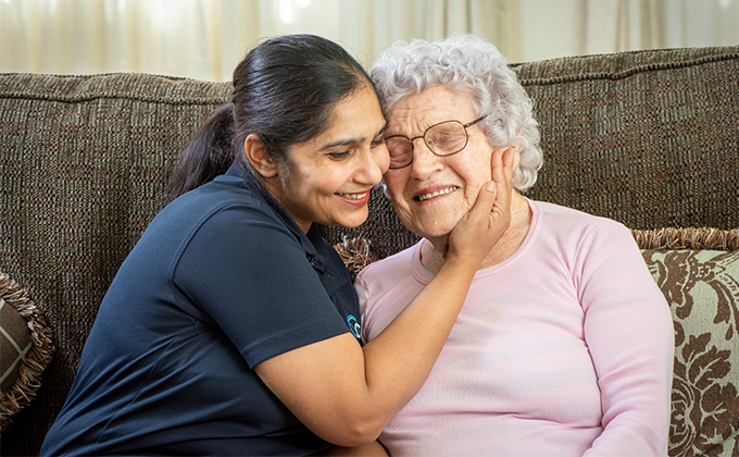 Resident and carer smiling and embracing on couch at Onkaparinga Valley Woodside nursing home