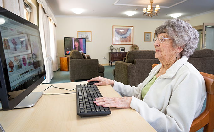 Resident using a computer at Onkaparinga Valley Woodside nursing home
